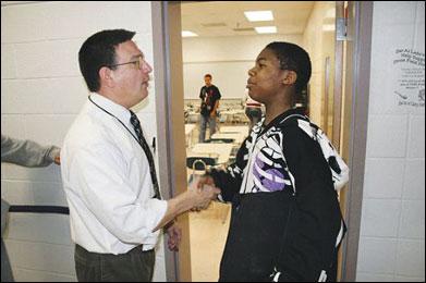 Teacher shakes hands at door.